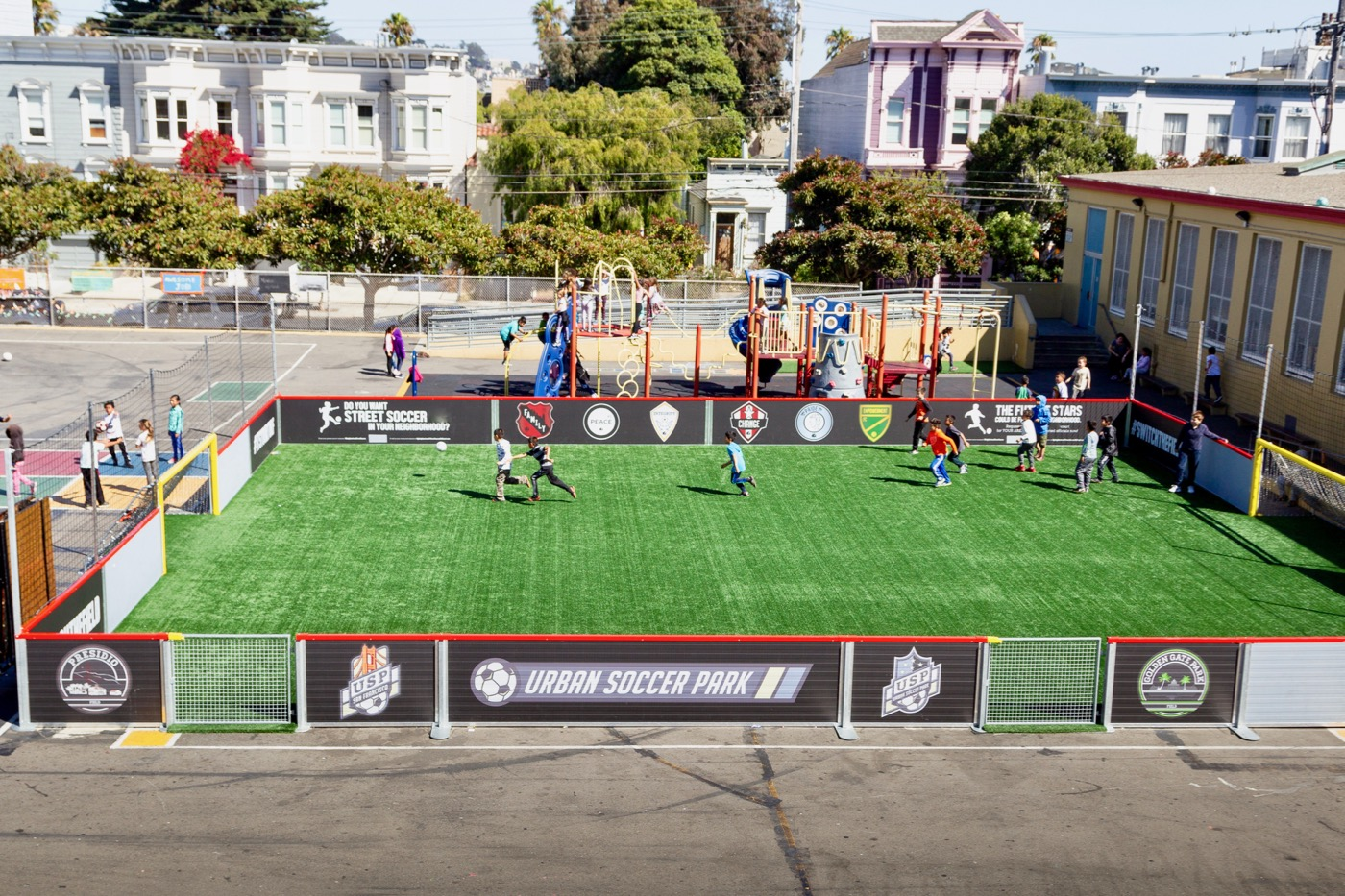 a mini pitch built in a school ground in san francisco with kids playing on it