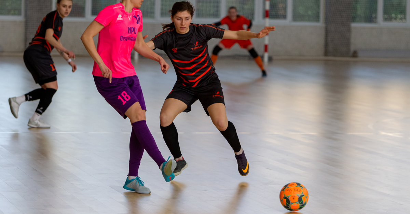 Futsal players play a game of futsal indoors