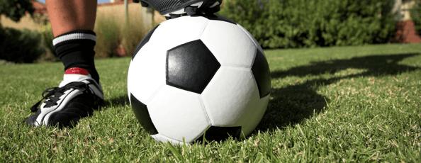 Mans foot on soccer ball on grass in backyard
