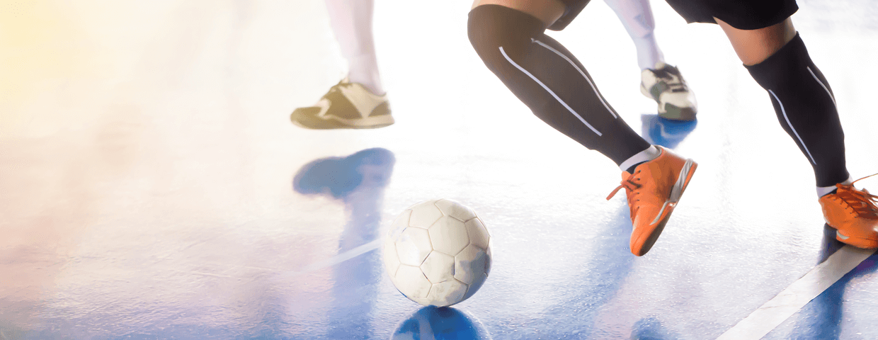 Indoor soccer, football, or futsal player on court, with soccer ball running and kicking with opponent near