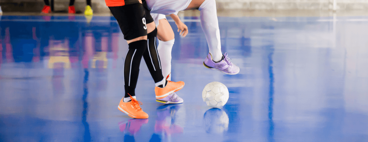 player trap and control of the ball to shoot a goal. Soccer players fighting each other by kicking the ball. Indoor soccer sports hall. Football futsal player, ball, futsal floor.